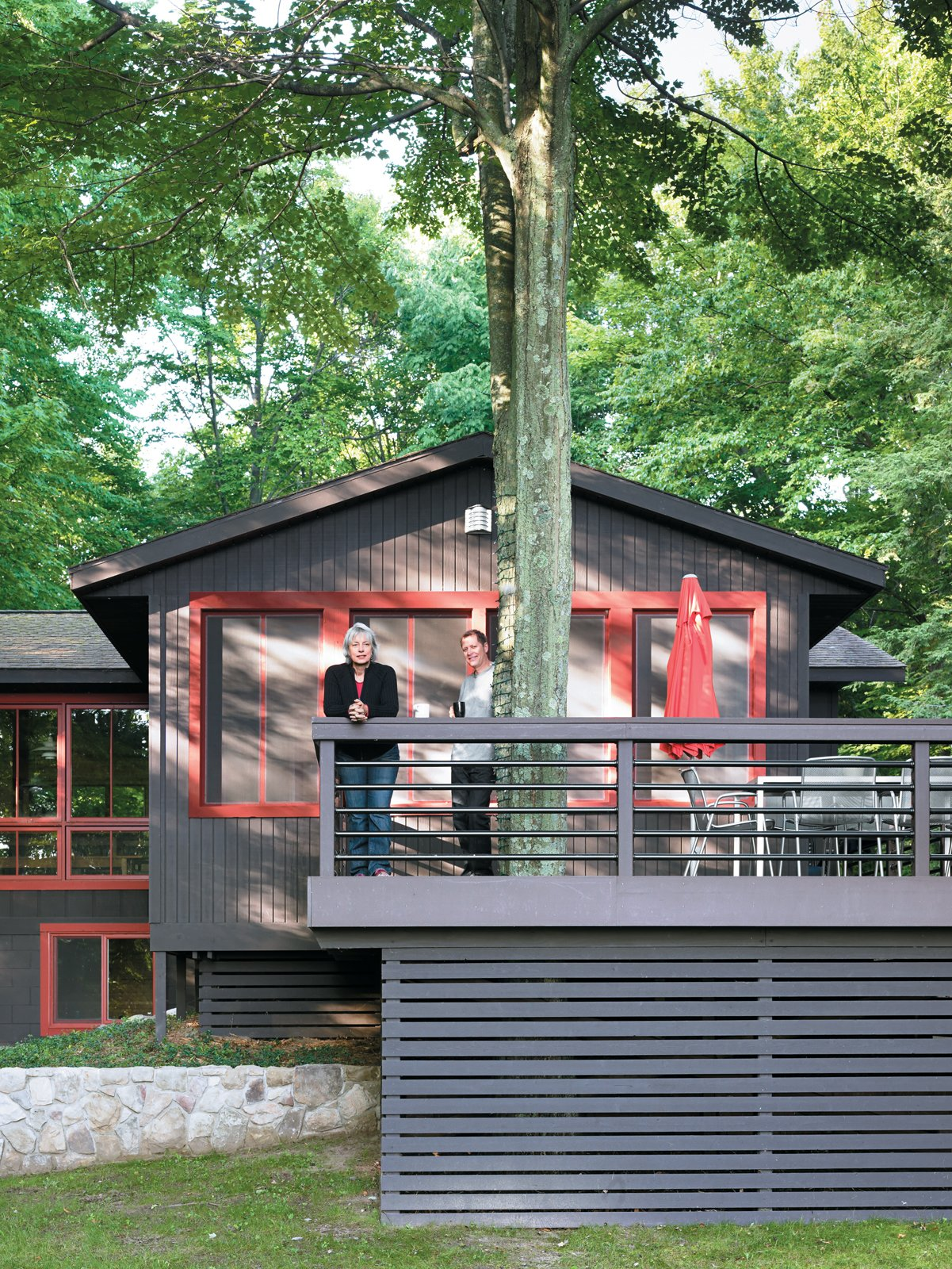 Built around the twin trunks of a maple tree, the Campbells' outdoor deck provides tranquil views of the lake and a chance for the family to spot roaming wildlife while enjoying their morning coffee. During warmer months, the wide space creates an ideal secondary dining room, shaded by the canopy of leaves overhead.  Photo 7 of 16 in 15 Brilliant Designs That Work Around Nature