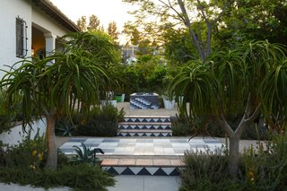In this garden by Mark Tessier, tiled stairs with a modern pattern bring a geometric and playful touch to this traditional home.