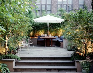 Elysian Landscapes modernized a classic brownstone by creating a private bi-level patio with clean, built-in seating for outdoor dining.