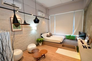10 Modern and Stylish Places to Stay in Hong Kong - Photo 10 of 10 - With a double bed on a raised wooden platform, white-washed brick walls, and Tom Dixon pendant lights, this 313-square-foot studio apartment is perfect for single travelers or couples.