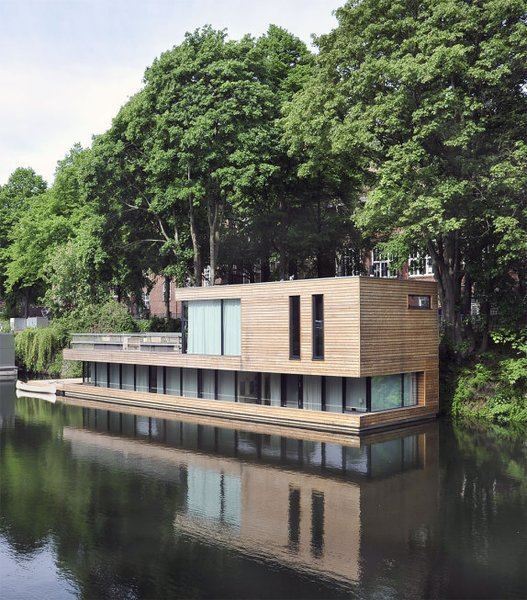 In Hamberg, Germany, Houseboat on the Eilbekkanal is enveloped in sliding timber slats, creating a constant connection between the interior and the exterior. Tagged: Exterior, Flat RoofLine, Boathouse Building Type, and Wood Siding Material.  Photo 2 of 11 in 10 Modern Floating Homes That Offer an Aquatic Lifestyle