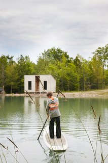 Cooper, 11, <br>paddleboards toward an outbuilding that contains a sauna.