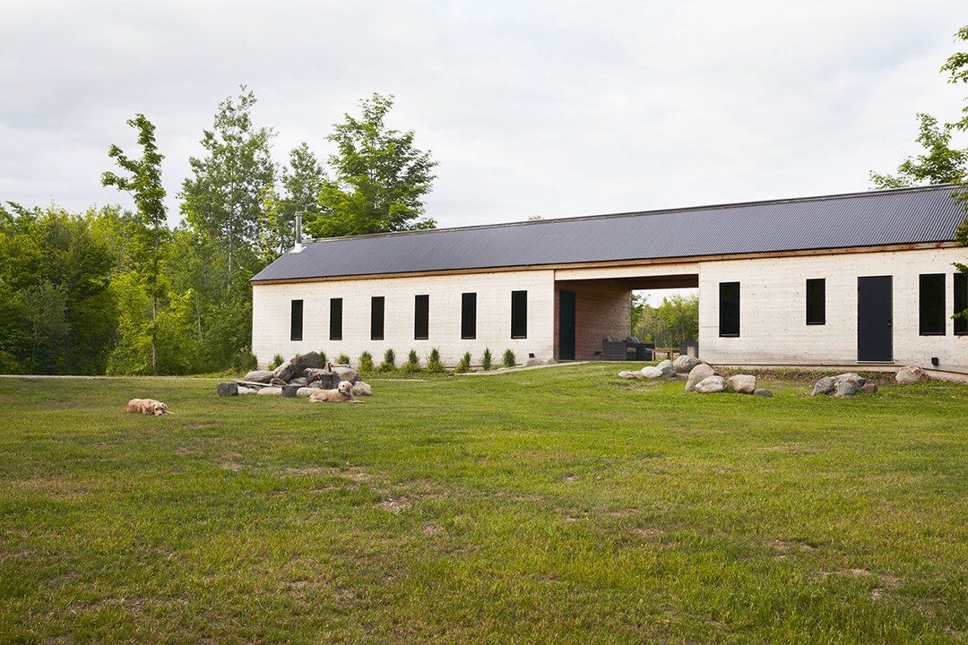 Exterior, Gable RoofLine, and House Building Type The east-west breezeway divides  the home into nearly equal halves: 700 square feet for bedrooms,  a bathroom, and the laundry, and 650 square feet for everything else.  To focus attention on the back­country wilderness, the team relied upon a restrained mix of materials, including tongue-and-groove cedar siding and a Vicwest corrugated-metal roofing product that is more commonly used for agri­cultural buildings.  Photo 6 of 11 in Hot to Trot