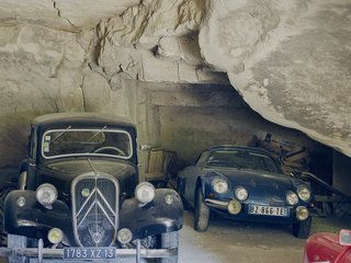The fleet includes a ruby-red Renault Dauphine and a black Citroën Traction Avant.