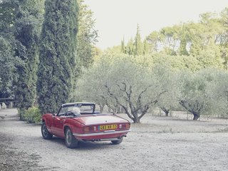 Lolo eases his Triumph Spitfire convertible, designed by Giovanni Michelotti, into the driveway.