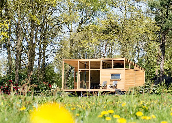 Surrounded by forests and meadows, this modern, minimalist cabin in Lettele, Netherlands is a prefab project by Dutch designers owners and designers Arno Schuurs and Paulien van Noort. The smart and sustainable layout incorporates large windows that bring the outdoors in. Materials such as untreated Oregon pine planks, oak fishbone flooring, concrete and raw steel were used to keep construction footprint low.  Photo 10 of 10 in Get Back to Basics by Staying at One of These Modern Cabins