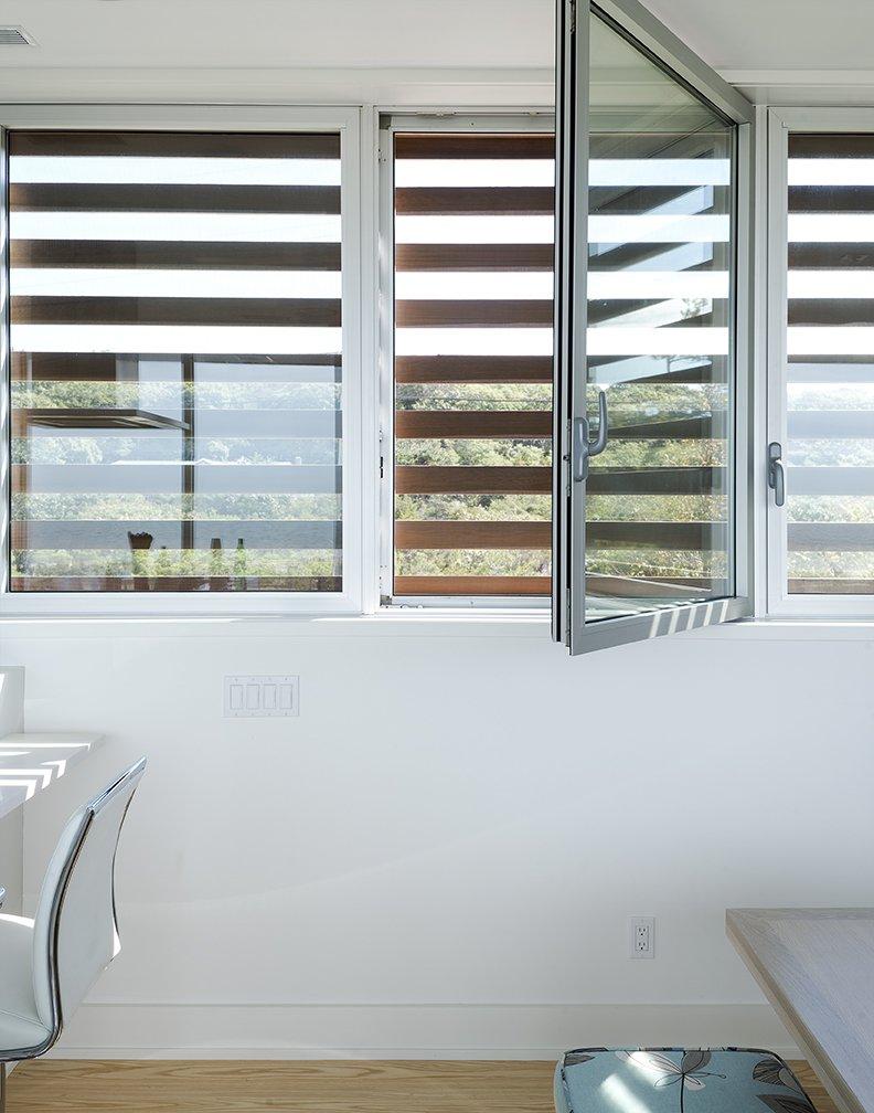 Cedar louvers veil hurricane windows by Solar Innovations.