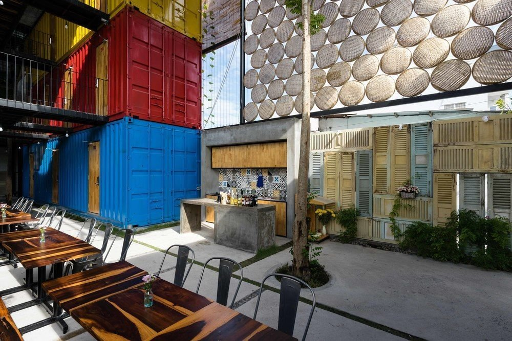 Dining Room, Bar, Chair, Wall Lighting, Concrete Floor, and Table Stacked shipping containers – painted red, blue and yellow to distinguish the different room types – are arranged around a large socializing area for guests.  Photo 2 of 7 in 6 Well-Designed Hostels For the Minimalist Traveler