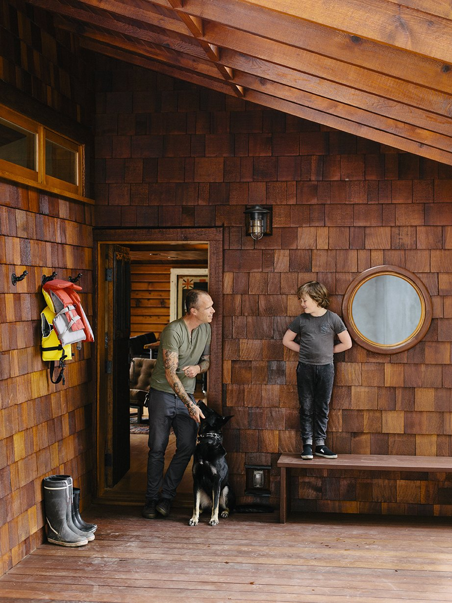 Outdoor, Front Yard, Small Patio, Porch, Deck, and Wood Patio, Porch, Deck At the entrance, Bruce is joined by his son, Sozé, and dog, Izzy. The 1940s shingled cottage was renovated by architectural designer Randall Recinos, designer Brian Paquette, and contractor Dylan Conrad.  Photo 1 of 13 in An Eclectic Pacific Northwest Cottage