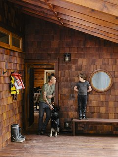 45 Pets in Beautiful Modern Homes - Photo 1 of 45 - At the entrance, Bruce is joined by his son, Sozé, and dog, Izzy. The 1940s shingled cottage was renovated by architectural designer Randall Recinos, designer Brian Paquette, and contractor Dylan Conrad.