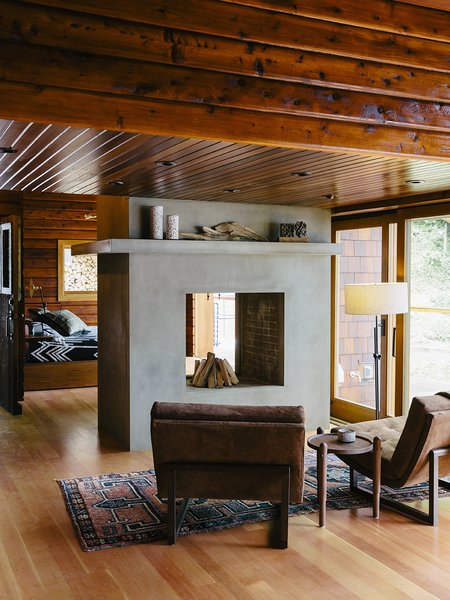 Bruce Livingstone's seaside getaway in British Columbia features a remarkably open layout. The master bedroom flows into the living room, where Griffin lounge chairs by Lawson-Fenning face a fireplace clad in glass fiber–reinforced concrete panels by Wiersma Masonry.