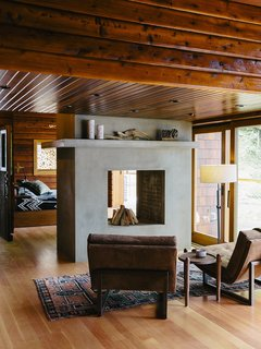 An Eclectic Pacific Northwest Cottage - Photo 2 of 13 - Bruce Livingstone's seaside getaway in British Columbia features a remarkably open layout. The master bedroom flows into the living room, where Griffin lounge chairs by Lawson-Fenning face a fireplace clad in glass fiber–reinforced concrete panels by Wiersma Masonry.