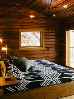 The master bedroom's <br>custom bed has built-in storage. The lighting is by Workstead.