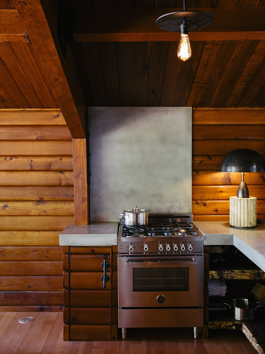 Kitchen, Wood Cabinet, Concrete Counter, Range, Ceiling Lighting, and Table Lighting A Column lamp by Apparatus and concrete countertops join a Bertazzoni propane range. The brass pendant is by Workstead.  Photo 5 of 13 in An Eclectic Pacific Northwest Cottage