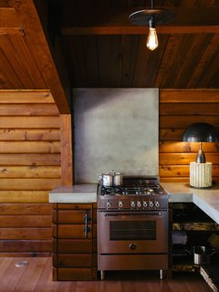 A Column lamp by Apparatus and concrete countertops join a Bertazzoni propane range. The brass pendant<br>is by Workstead.