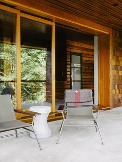 An Eclectic Pacific Northwest Cottage - Photo 9 of 13 - Sling chairs by Garza Marfa flank <br>a Made Goods concrete table.