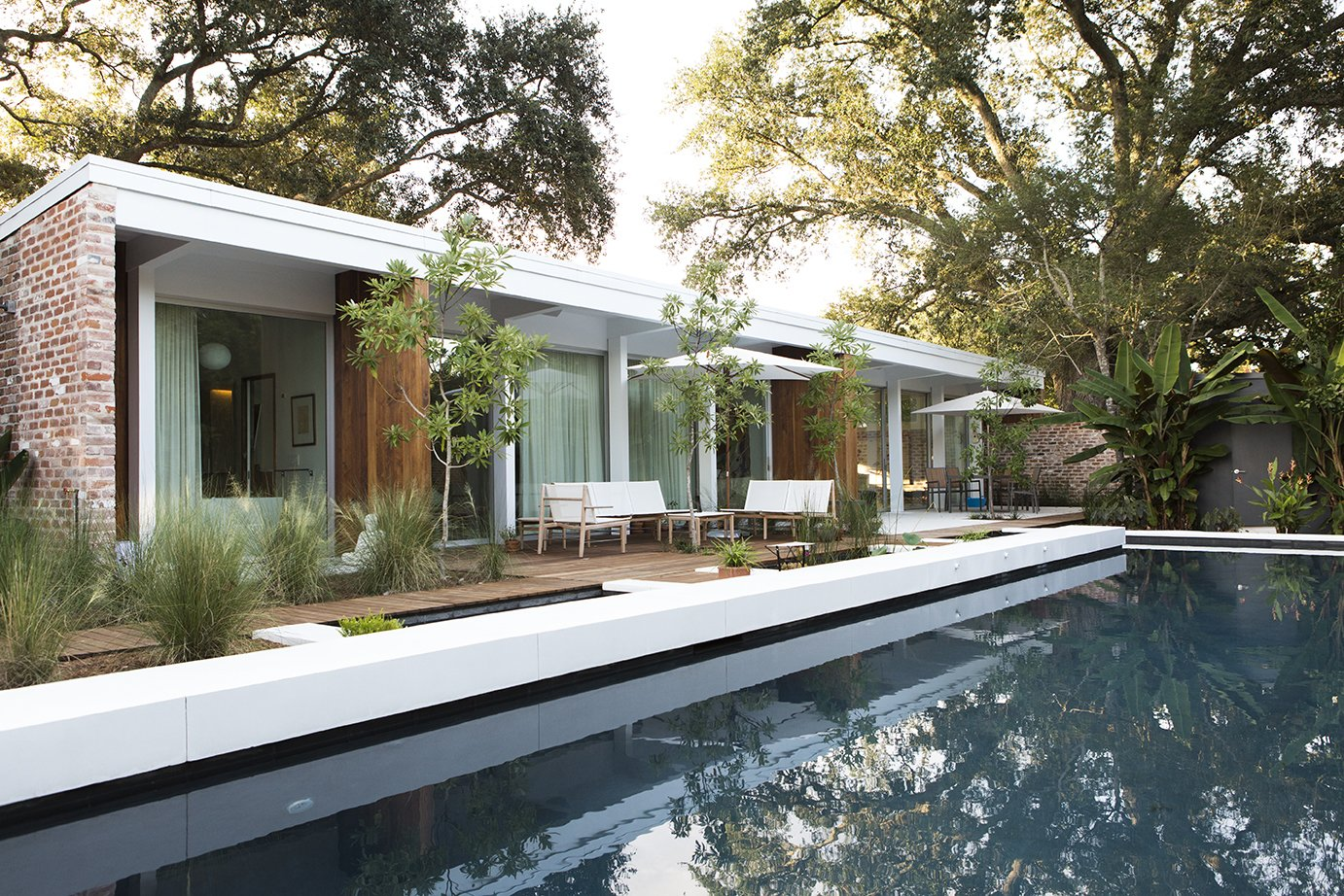 Outdoor, Large Pools, Tubs, Shower, Swimming Pools, Tubs, Shower, Large Patio, Porch, Deck, and Wood Patio, Porch, Deck To revive the original architects' vision, studioWTA restored a four-foot roof overhang above a wall of La Cantina sliders. The shade helps limit solar gain, while a pool by Evans + Lighter Landscape Architecture provides respite on sweltering summer days.  Photo 7 of 13 in Back to the Garden