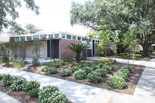 "Plantings: Evans + Lighter Landscape Architecture, contractor Sandra Tomasetti, and architecture firm studioWTA collaborated to develop a roofline without gutters above the walkway and carport. Instead, water is channeled to feed the garden. The result is a California-inspired yard with geometrically laid-out plantings rather than grass. ""It's rows of green with mulch permeating,"" Maury says."