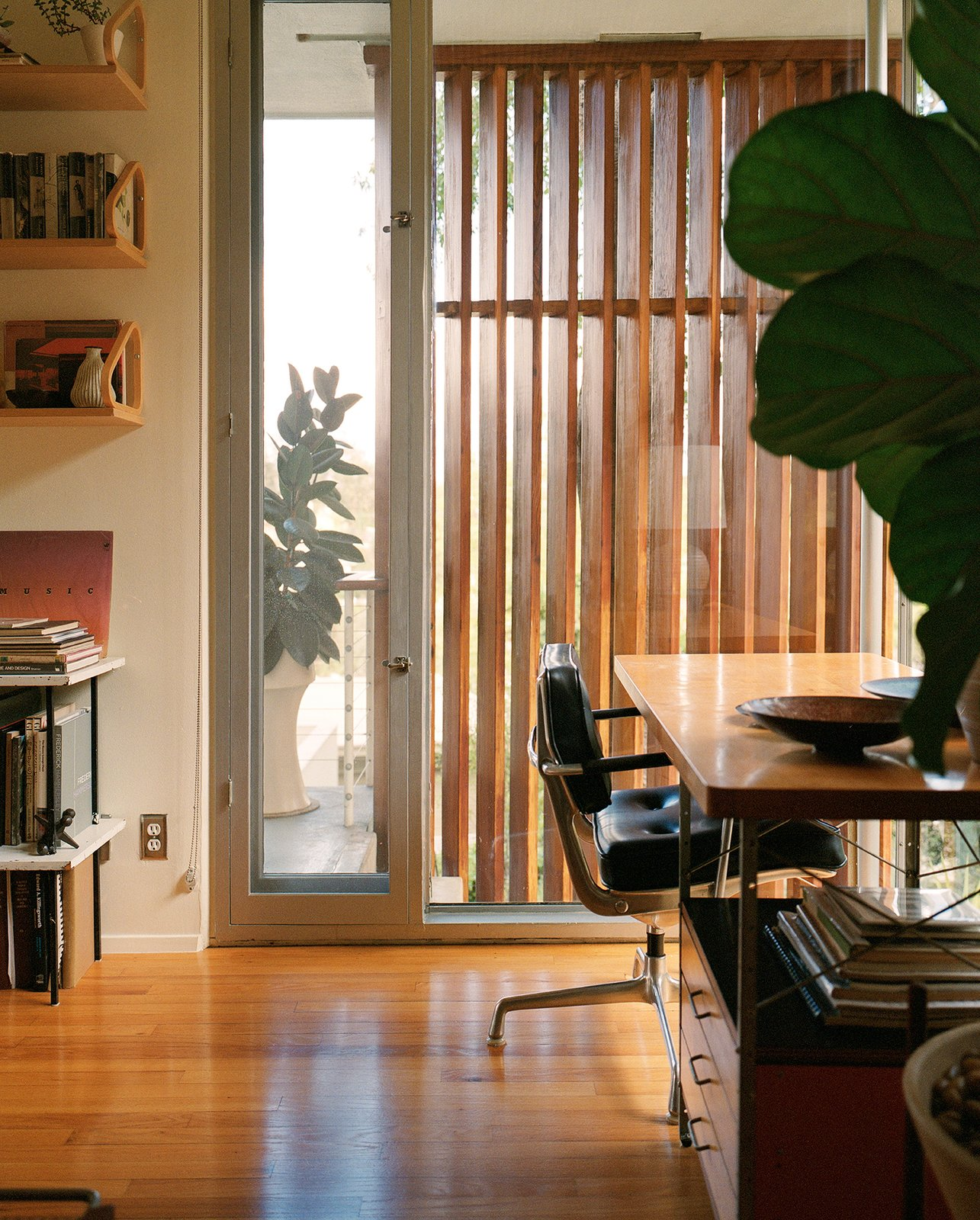 """Office, Study Room Type, Chair, Storage, Shelves, Desk, and Medium Hardwood Floor The den's first-production Eames Desk Unit (EDU) was """"rescued"""" from a Gregory Ain house.  Photo 6 of 14 in In Search of Alvin Lustig"""