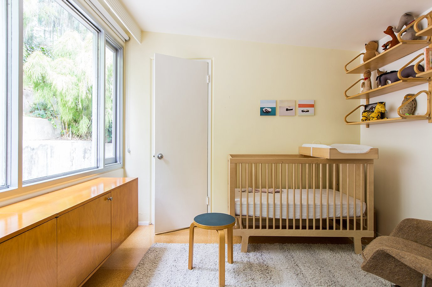 Bedroom, Bed, Chair, Storage, Shelves, Medium Hardwood Floor, and Rug Floor A floating cabinet was created by Lustig in 1953 for an interior design commission in New Jersey. The Sparrow crib is by Oeuf.  Photo 10 of 14 in In Search of Alvin Lustig