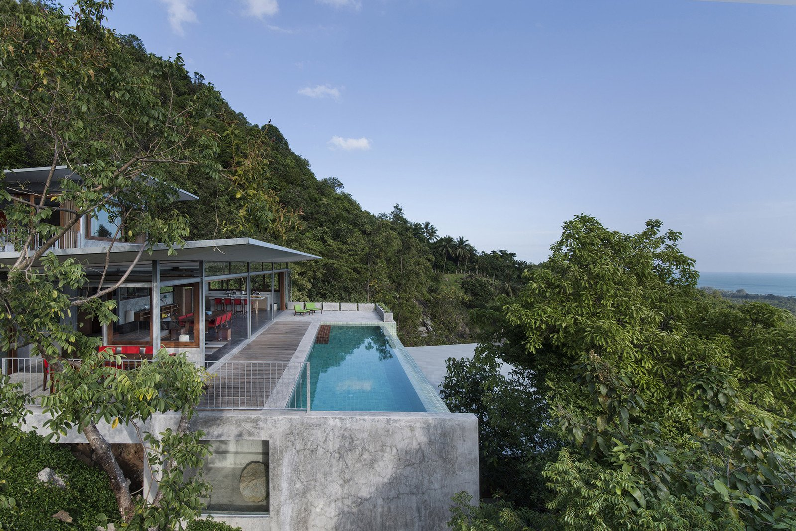 Infinity Pools, Tubs, Shower, Wood Patio, Porch, Deck, Trees, Back Yard, Metal Fences, Wall, Outdoor, Slope, and Swimming Pools, Tubs, Shower  Photos from Take a Trip to This Photographer-Designed Concrete Home in Thailand
