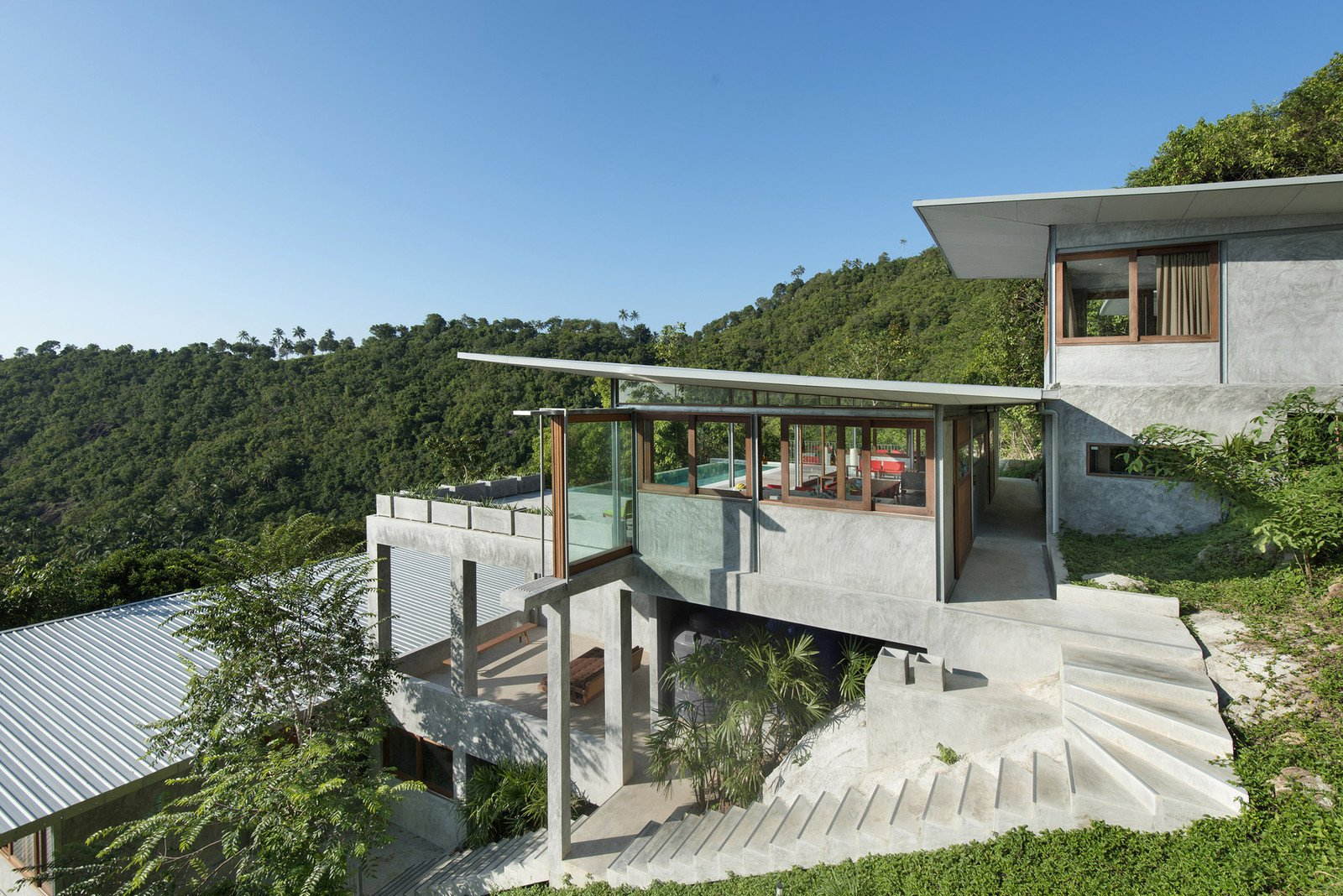 Sofa, Bed, Trees, Metal, Side Yard, Cooktops, Freestanding, Enclosed, One Piece, Outdoor, Slope, Shrubs, Walkways, and Grass  Best Outdoor One Piece Sofa Photos from Take a Trip to This Photographer-Designed Concrete Home in Thailand