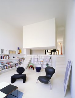 "The bedroom in this conversion of a former artist's studio is literally concealed in a white box suspended from the ceiling and located just off the living room. Designed by Emmanuel Combarel Dominique Marrec Architects, the bedroom is ""like a hut in the middle of the flat."""