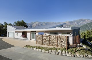 Solar panels are affixed to the garage roof, which is angled to maximize exposure.