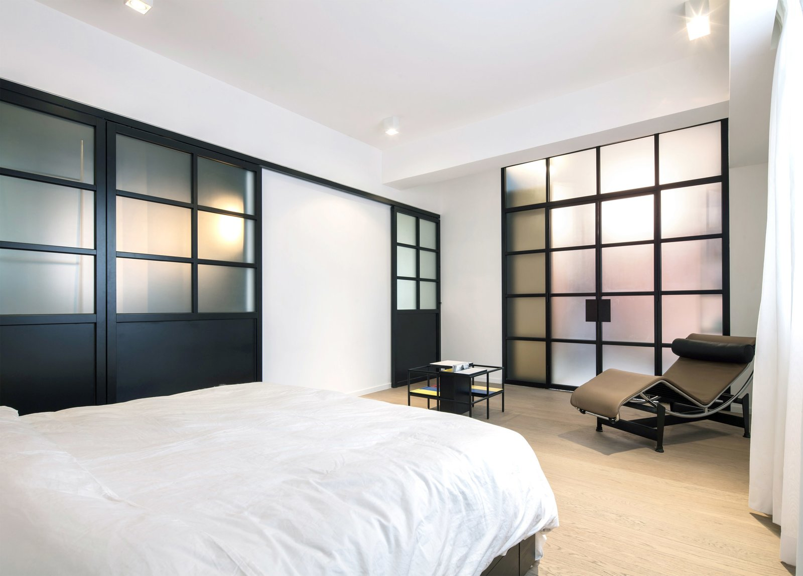 Bedroom, Chair, Ceiling Lighting, Bed, and Light Hardwood Floor  Photo 5 of 7 in See How This Colorful Hong Kong Apartment Was Made to Feel Bigger Than it Actually Is
