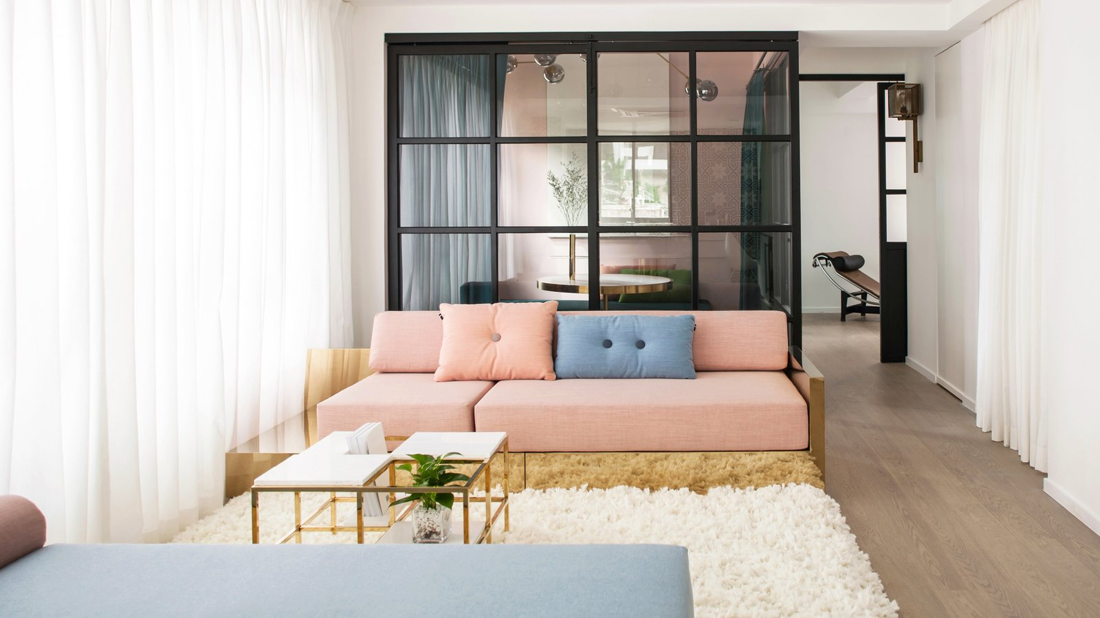 Living Room, Sofa, Medium Hardwood Floor, and Coffee Tables  Photo 3 of 7 in See How This Colorful Hong Kong Apartment Was Made to Feel Bigger Than it Actually Is