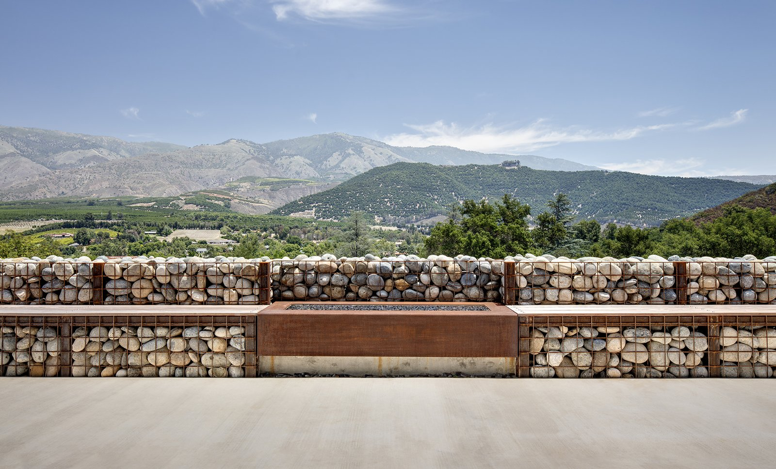 Walkways, Outdoor, Front Yard, Stone Patio, Porch, Deck, Concrete Patio, Porch, Deck, Metal Patio, Porch, Deck, and Vertical Fences, Wall The gabions hold smooth rocks from the nearby San Luis Rey River; a fireplace feature is flanked by benches.  Photo 5 of 5 in Mountain Song