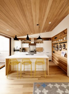 Swell lights by Pablo hang above Hot Mesh stools from Blu Dot. The millwork is by J. Spix Fine Cabinets.