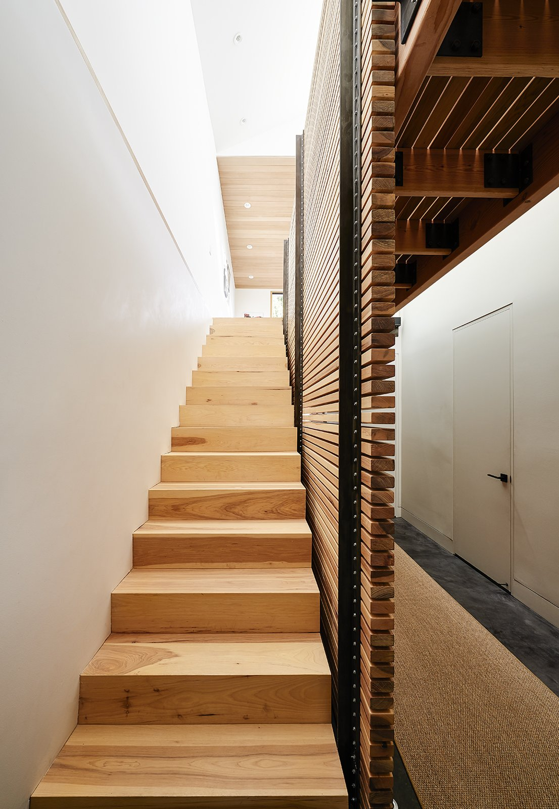 Wood Tread and Exterior By eliminating the attic and carving out a former crawl space, Red Dot Studio created room for the residents' bedrooms underneath the primary living areas. The slatted-hickory-and-glass bridge allows light from a row of skylights to penetrate deep into the lower level.  Photo 4 of 9 in A Renovated Tiny Victorian with 21st-Century Interiors
