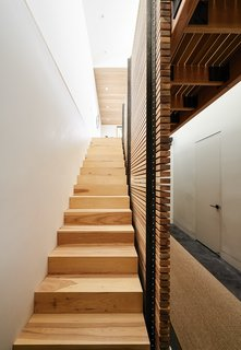 By eliminating the attic and carving out a former crawl space, Red Dot Studio created room for the residents' bedrooms underneath the primary living areas. The slatted-hickory-and-glass bridge allows light from a row of skylights to penetrate deep into the lower level.