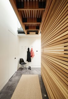 The lower level is distinguished by stained concrete flooring. In the hallway, <br>a Molded Plastic Chair by Charles and Ray Eames for Herman Miller offers a place for the residents to remove their coats and shoes. The seat has an Eiffel base.