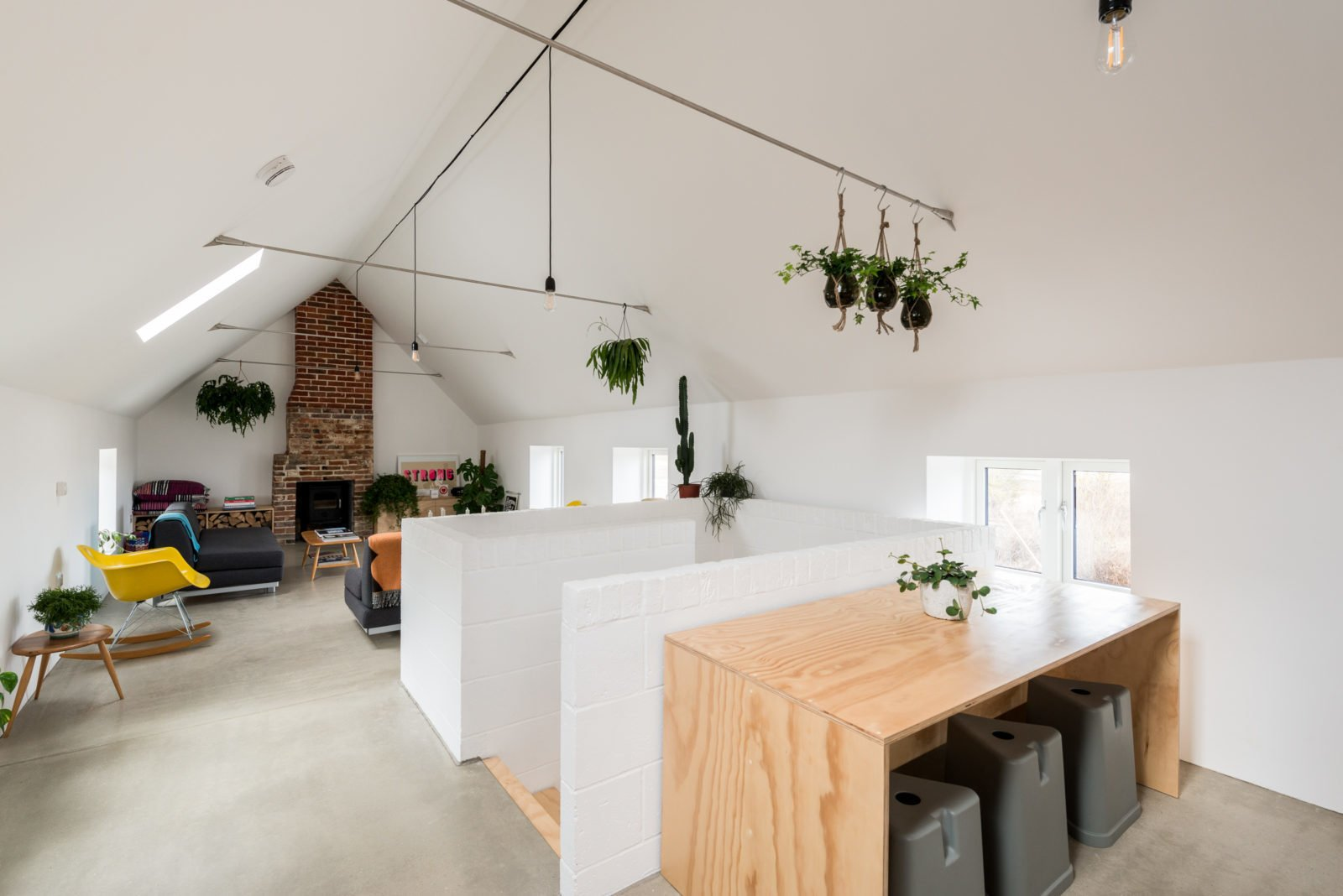 Living Room, Concrete Floor, End Tables, Wood Burning Fireplace, Pendant Lighting, Sofa, Chair, and Standard Layout Fireplace  Photo 8 of 19 in 10 Dwell-Approved, New-Old Homes in the UK from Formerly a Farm Workers' Cottage, This Cool Norfolk Home Costs Just Over $1 Million