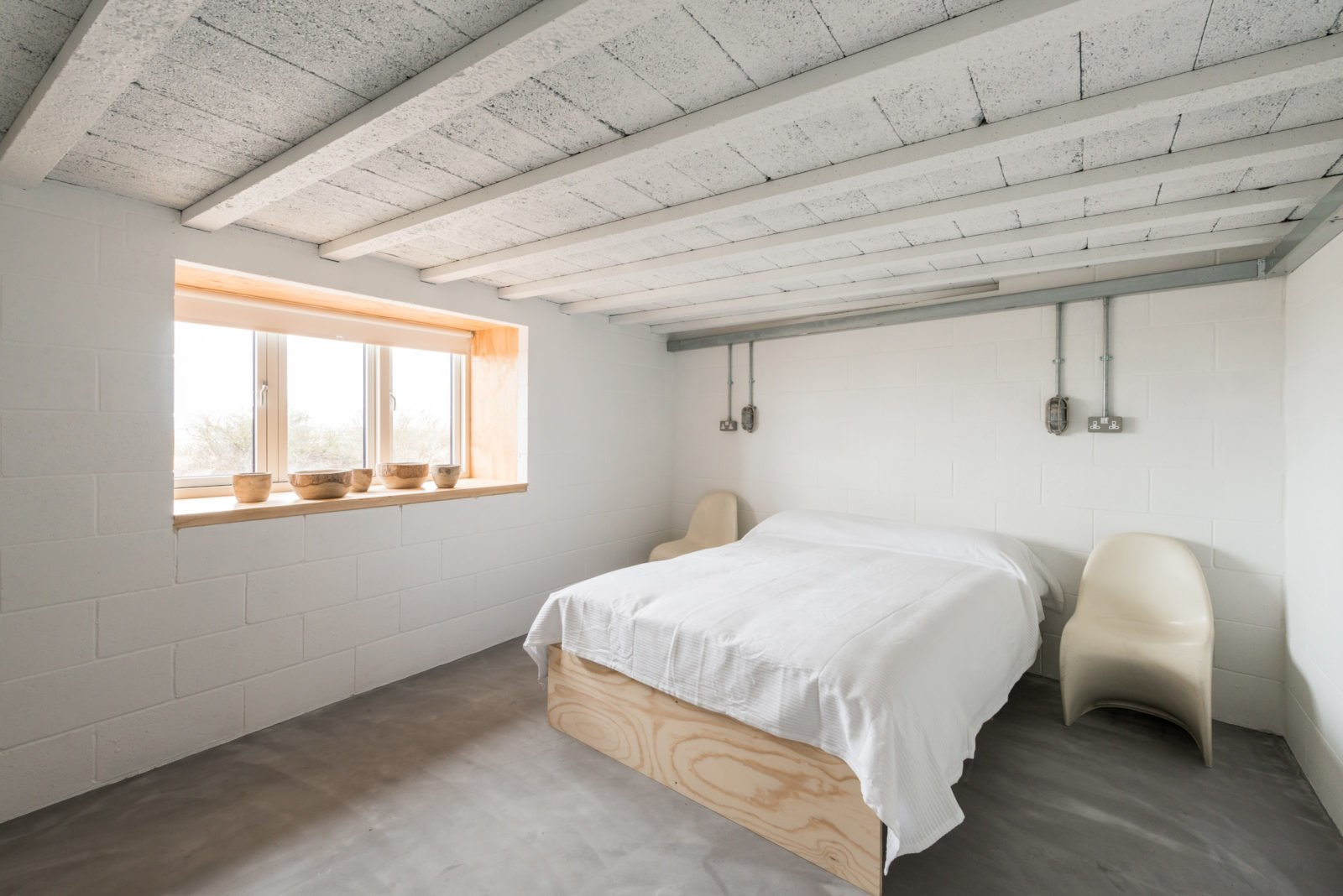 Bedroom, Chair, Bed, and Concrete Floor  Photo 4 of 11 in Formerly a Farm Workers' Cottage, This Cool Norfolk Home Costs Just Over $1 Million