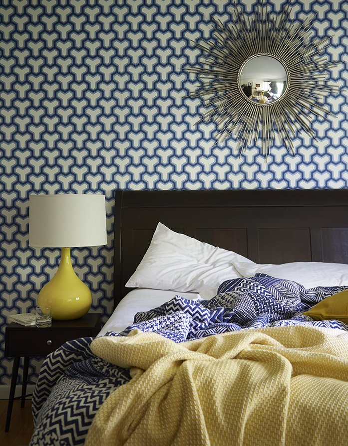 Bedroom, Night Stands, Table Lighting, and Bed A sunburst mirror, which George bought on eBay, pops against patterned Antonina Vella wallpaper in the guest bedroom. The lamp is vintage.  Photo 13 of 13 in How to Update a Midcentury Modern Gem