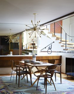 Mostly they restored original elements, like the buffet and the staircase. Cherner chairs sit at the head of a Design Within Reach table. The armless Series 7 chairs are by Arne Jacobsen; the third pair are Juliana chairs by Aristeu Pires.