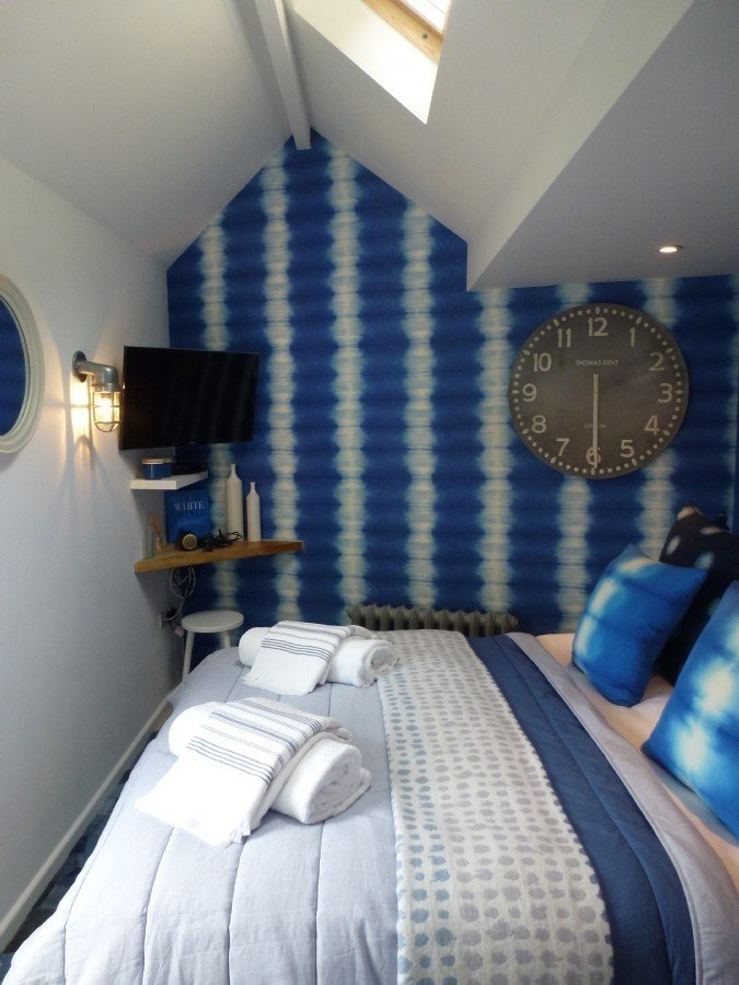 Inspired by the shimmering blue sea just outside its doorstep, The Ink in the village of Saint Agnes in Cornwall is a bold, boho-coastal holiday retreat with tie-dye wallpapers and plenty of blue everywhere.  Photo 5 of 10 in 9 Small Spaces With  Color