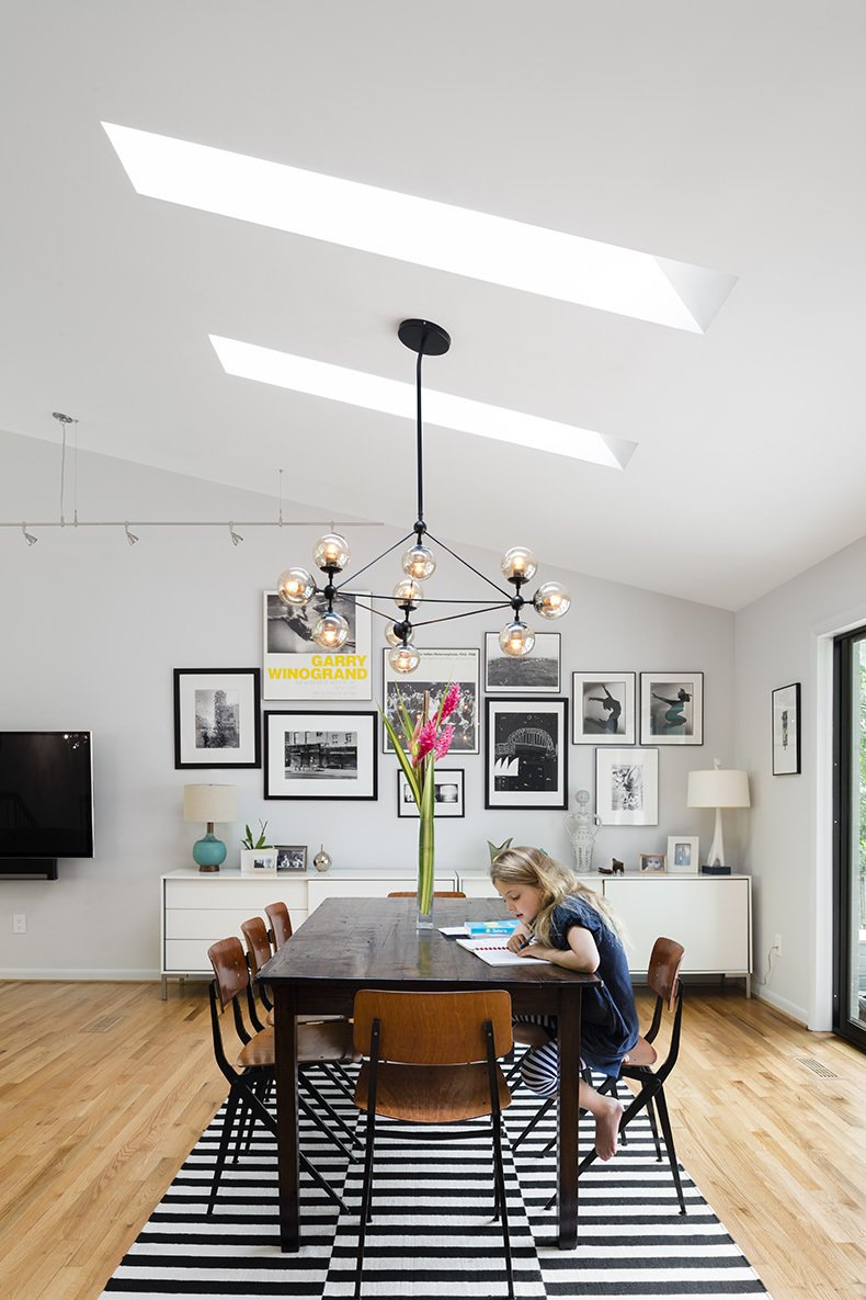 The dining area (above right) boasts circa-1955 Friso Kramer chairs. Tagged: Dining Room, Ceiling Lighting, Table, Light Hardwood Floor, Chair, Storage, and Shelves.  Photo 4 of 8 in Minor Adjustments