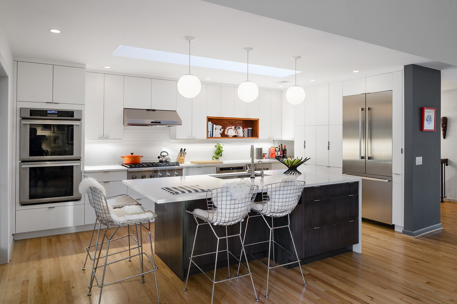 Kitchen, White Cabinet, Refrigerator, Medium Hardwood Floor, Wall Oven, Ceiling Lighting, Range, Range Hood, and Drop In Sink In the renovated kitchen space, Dianne chose quartz counters in Blizzard by Caesarstone.  Photo 5 of 8 in Minor Adjustments