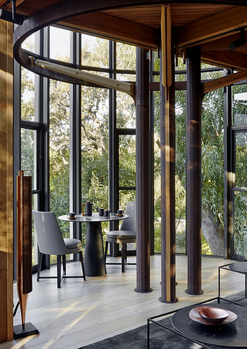 Dining Room, Table, Chair, and Medium Hardwood Floor The tree house–inspired design mimics the surrounding woods. On each floor, steel rings and columns support Western red cedar floor joists above.  Photo 3 of 9 in A Floating South African Cabin Borrows From the Landscape