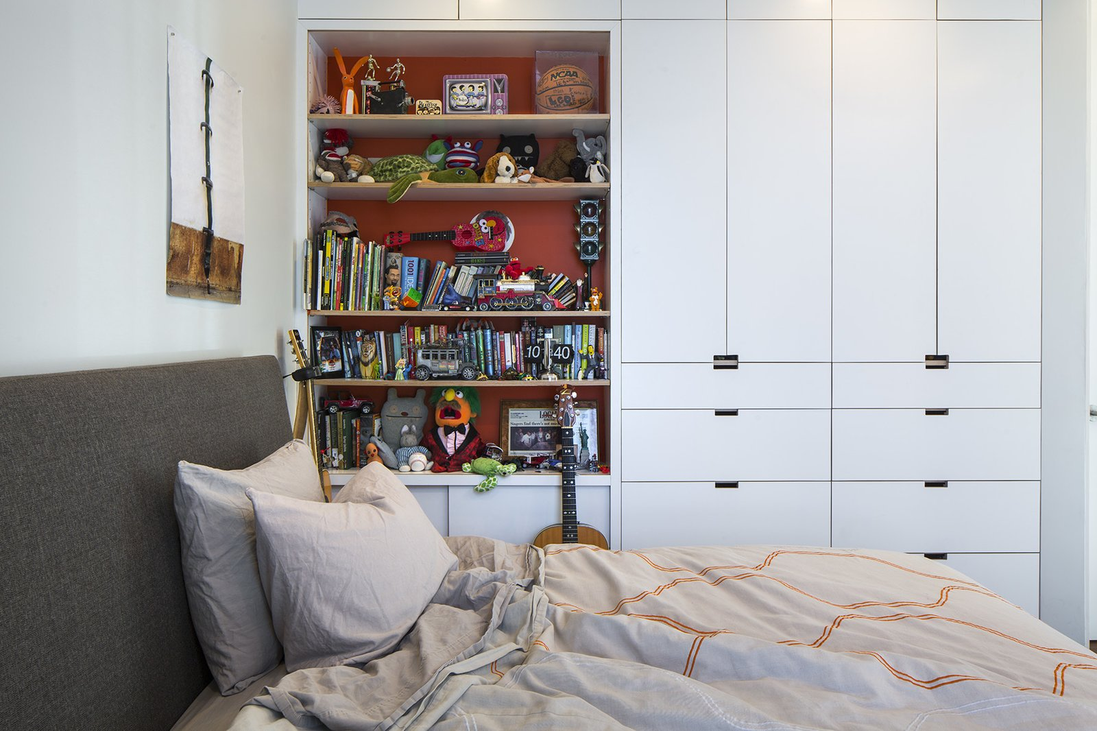 Bedroom, Bookcase, Storage, and Wardrobe Built-in storage keeps things organized in Leo's bedroom, which contains an Ella bed from Room & Board and an Inmod duvet.  Photo 7 of 12 in A Southern Californian Prefab Is Paradise For the Whole Family