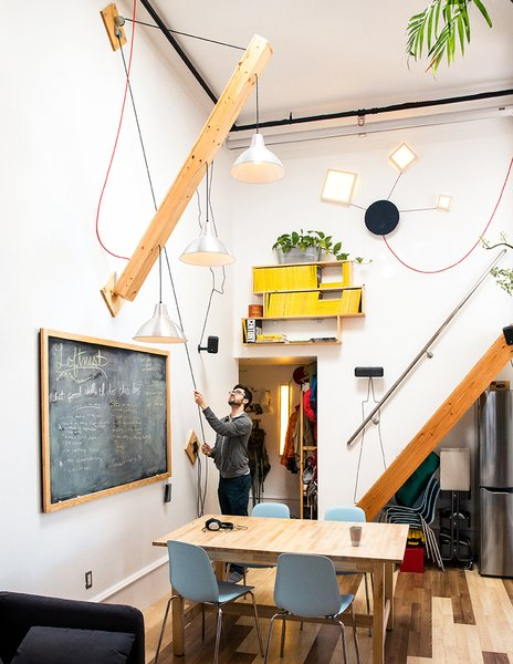 """Max devised a movable plywood beam that holds a trio of pendant lamps to swing down as needed. A wood piece covered in chalkboard paint hides the electrical panel. """"Slate was too expensive,"""" he says."""