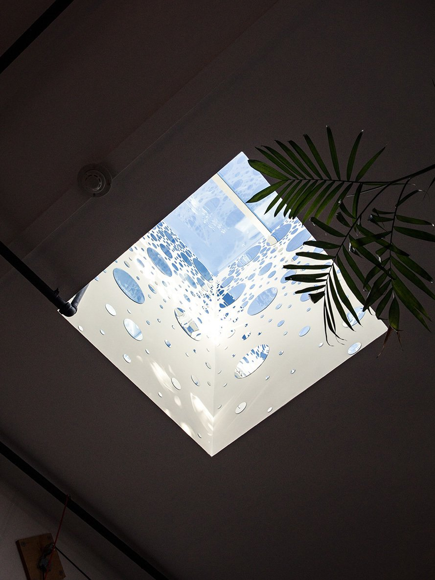 Windows Circular mirrors adhere to the inner walls of a skylight above the dining area, bouncing light and bringing the room yet more illumination.  Photo 4 of 11 in Devising Clever Solutions For a Small San Francisco Loft