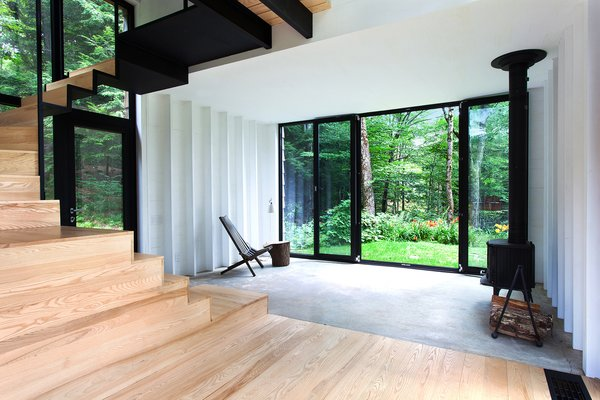 The addition rises above the original shack's 400-square-foot concrete foundation, which is partially visible in the living room. A Cricket patio chair by Hershy Way is used for indoor seating opposite a Morsø wood-burning stove.
