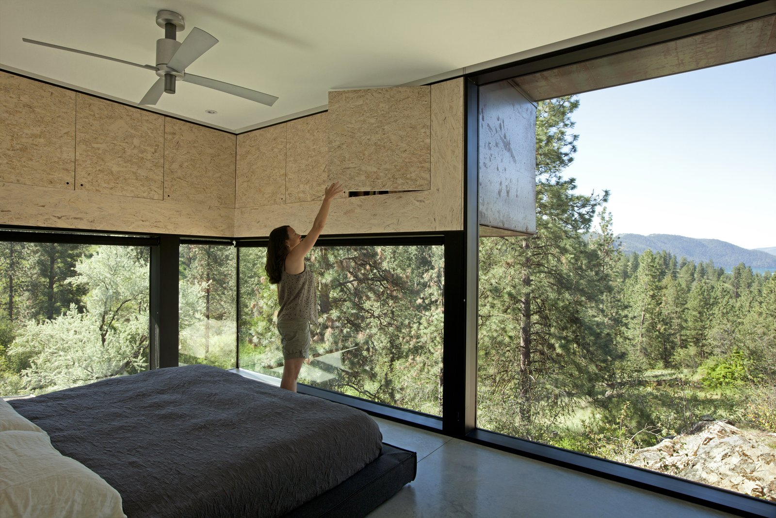 Bedroom, Bed, and Concrete Floor Protruding overhead cupboards increase storage space and reduce solar gain. The bed is Dodu by Blu Dot.  Photo 8 of 11 in A Hilltop Home in British Columbia That Seems to Grow Out of a Park