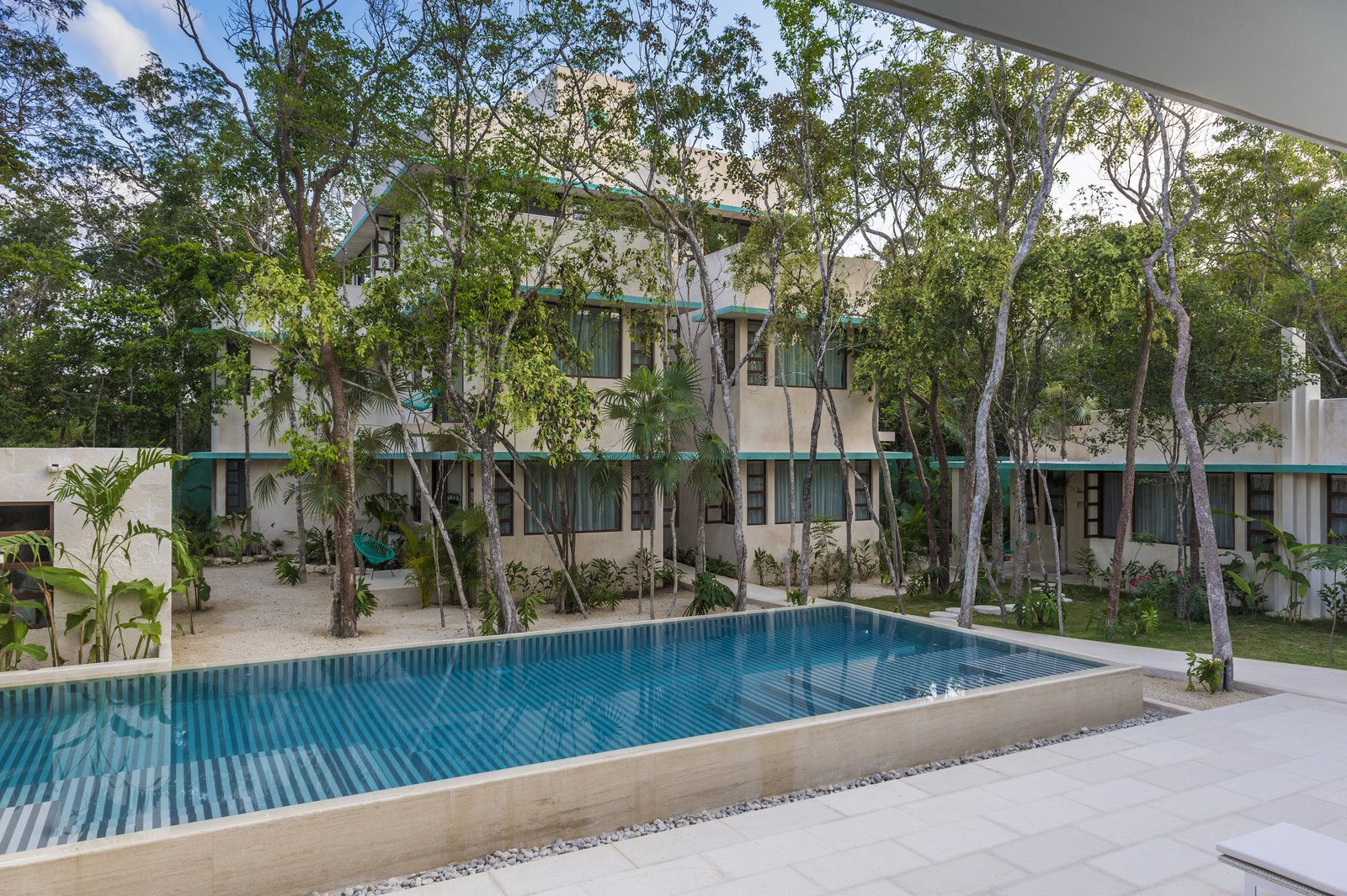 Outdoor, Back Yard, Trees, Large Pools, Tubs, Shower, and Swimming Pools, Tubs, Shower  Photo 4 of 9 in A New Modern Hotel Brings Midcentury Miami to Tulum, Mexico