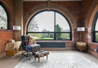 The facade is punctuated by windows of various shapes, including half-moons by Crittall. The armchair and chevron rug are from Graham & Green.